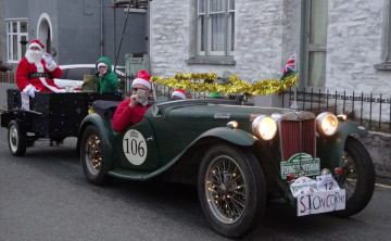 December photo of old green MG car, with trailor on the back with Father Christmas