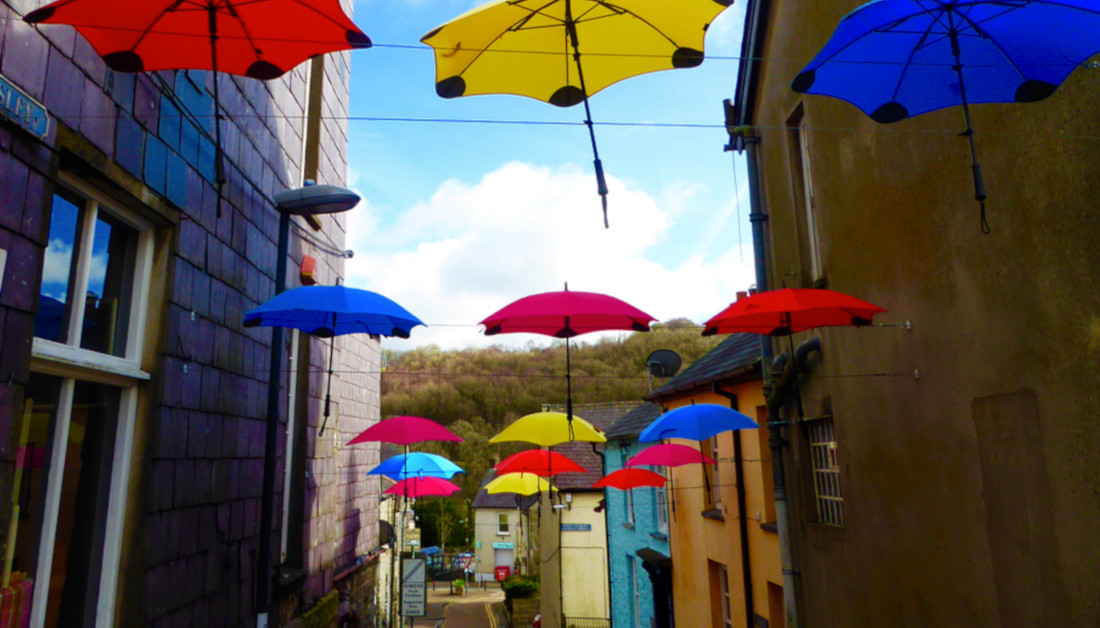Umbrella Canopy. Red, yellow and blue umbrellas hanging from a canopy in Llandysul, Ceredigion.