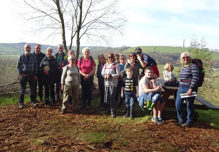 Group of walkers standing together, in front of view over valley and at opposing hillside.